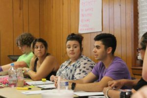 Carlos Vela shares an idea with the rest of the group during a brainstorming session at the YLC summer training.
